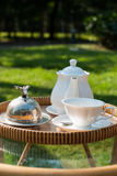 Wicker chairs and table with tea set Royalty Free Stock Image