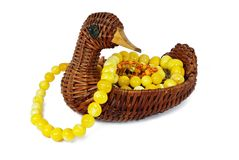 Wicker contaimer in form of duck with beads. Wicker container in form of duck with amber beads on white background Stock Image