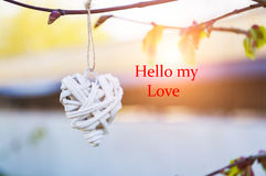 Wicker country heart hanging from tree branch. Valentines Day. Blurred background and inscription Hello my love. Wicker country heart hanging from tree branch Stock Images