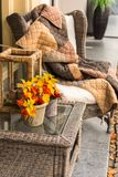 Wicker cozy armchair with blanket and small wicker glass table Stock Images