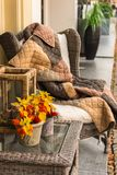 Wicker cozy armchair with blanket and small wicker glass table Royalty Free Stock Photos