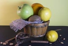 Wicker decorative cart with fruits. Orange, lemon, kiwi, apple Royalty Free Stock Images