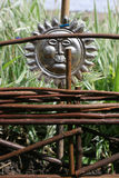 Wicker Fence Panel. A section of a  hand made Wicker Fence Panel in an urban garden with a metalic sun styled bird scarer to background. Green foliage to Royalty Free Stock Photo