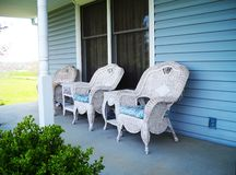 Wicker Furniture. White wicker furntiture with blue cushions, look refreshing on a house with blue siding and white trim Royalty Free Stock Images