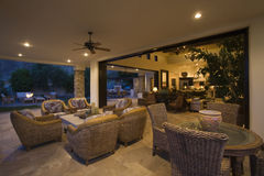 Wicker Furniture In Lit Home. Wicker furniture in lit spacious home with porch view at night Royalty Free Stock Photo