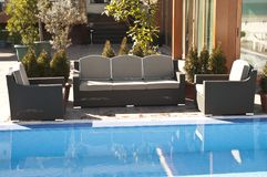 Wicker furniture sets by the pool. Brown wicker furniture sets by the pool with coffe table, brown cushion stock photo