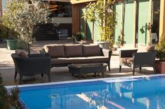 Wicker furniture sets by the pool. Brown wicker furniture sets by the pool with coffe table, brown cushion stock photos