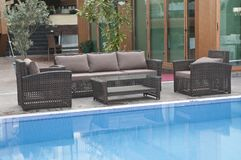 Wicker furniture sets by the pool. Brown wicker furniture sets by the pool with coffe table, brown cushion, closeup view royalty free stock photos