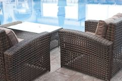 Wicker furniture sets by the pool. Brown wicker furniture sets by the pool with coffe table, brown cushion, closeup view stock image