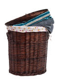 Wicker hamper. Full of dirty clothes over white background royalty free stock photography