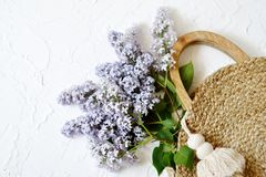 Wicker Handbag with Lilac Flowers , Spring Time, Summer Concept. White Background, Copy Space, Top View royalty free stock image