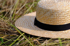 Wicker hat, hay, farm. High quality close up photo of a classic broad-brimmed hat: you may see classic wicker hat with dark almost black wide fabric strip around stock photography