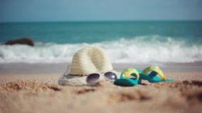 Wicker hat on the shore. Flip flops and sunglasses near the sea. Changes focus from splashing waves. Vacation concept stock footage