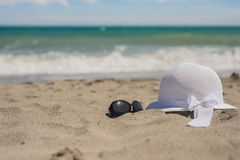 Wicker hat and sunglasses on the beach Stock Photo