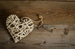 Wicker heart handmade with the key on a wooden base Stock Photo
