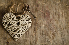Wicker heart handmade with the key on a wooden base Stock Photos
