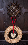 Wicker heart on old wooden medival door background Stock Images