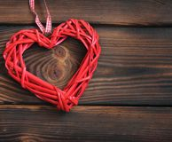 Wicker heart on a wooden background. Love stock image