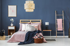 Wicker lampshade above bed Stock Photos