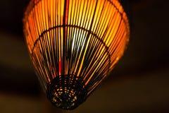 Wicker lantern thin vertical lines radiates orange light against a dark. Background Stock Photo