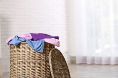 Wicker laundry basket with dirty clothes indoors. Space for text royalty free stock photo