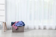 Wicker laundry basket with dirty clothes near window in room. Space for text royalty free stock photography