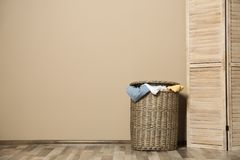 Wicker laundry basket full of dirty clothes on floor near wall. Space for text royalty free stock images