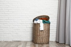 Wicker laundry basket full of dirty clothes near brick wall in room. Space for text royalty free stock images