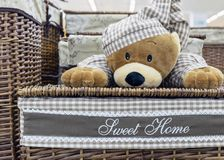 Wicker laundry basket with a teddy bear in checkered pajamas royalty free stock photo