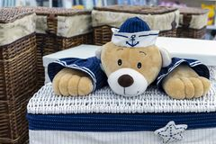 Wicker laundry basket with a teddy bear in marine uniform stock images