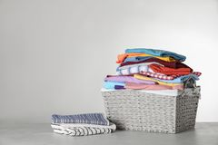 Free Wicker Laundry Basket With Clean Clothes On Table Against Light Background Stock Image - 151358571