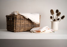 Wicker Linen basket on a shelf. Wicker Basket with linen inside, on a shelf with a rustic bottle and dried teasel plant Stock Photo