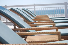 Wicker lounge chairs poolside by the beach Stock Photography