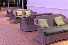 Wicker love seats. With cushions and pillows in low light on cruise ship deck Stock Photos
