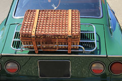 Wicker luggage on a classic car. Classic wicker suitcase on back side of an old car Stock Photos
