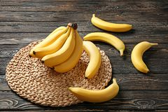 Wicker mat with yummy bananas. On wooden background Stock Photography