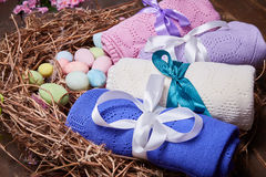 Wicker nest Easter set with colored eggs hay crocheted blankets covered with silk satin ribbon easter holy celebration, happy, pre. Sent Royalty Free Stock Photo