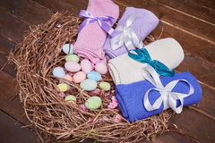 Wicker nest Easter set with colored eggs hay crocheted blankets covered with silk satin ribbon easter holy celebration, happy, pre. Sent Royalty Free Stock Images