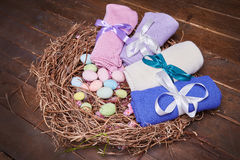 Wicker nest Easter set with colored eggs hay crocheted blankets covered with silk satin ribbon easter holy celebration, happy, pre. Sent Stock Photos