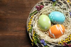 Wicker nest with painted Easter eggs and flowers on wooden table, top view. Space for text stock images