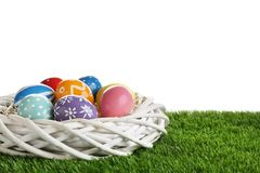 Wicker nest with painted Easter eggs on green grass against white background. Space for text royalty free stock photos