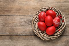 Wicker nest with painted Easter eggs on wooden table, top view. Space for text stock photos