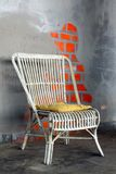 Wicker old armchair. With painted wall in background stock images