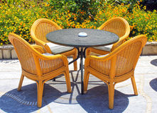 Wicker patio chairs and table in the garden Royalty Free Stock Images