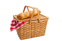 Wicker picnic basket with bread on white Royalty Free Stock Image