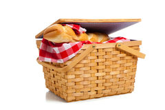 Wicker picnic basket with bread on white Stock Photography