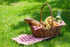 Wicker picnic basket with food and drink in a park. Summer picnic on the grass or lawn royalty free stock images
