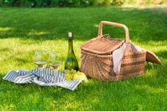 Wicker picnic basket, fruits and bottle of wine with glasses on napkin Royalty Free Stock Image