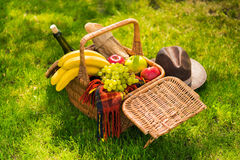 Wicker picnic basket with fruits and wine, plaid and hat on green lawn Stock Photos