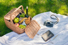 Wicker picnic basket with fruits and wine, vintage camera and notebook with pencil Stock Photography